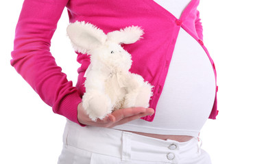 Belly of pregnant woman holding toy rabbit with unreal design