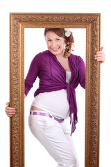 Happy pregnant woman with flower in hair poses in frame