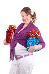 Pregnant woman with flower in hair holds two boxes with gift