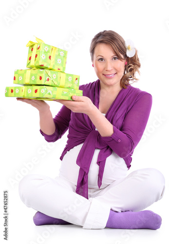 Happy pregnant woman sits on floor and holds green boxes