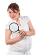 Pregnant woman in white with magnifying glass looks at camera