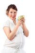 Pregnant woman in white holds cup isolated on white background.