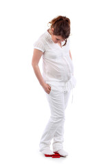 Pregnant woman in white stands on red balance and looks