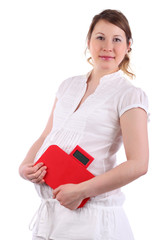 Pregnant woman in white holds red balance isolated on white