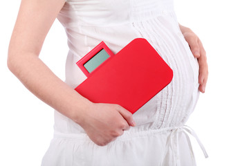 Belly of pregnant woman in white holding red balance isolated