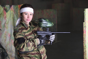 Woman in camouflage clothing with gun for paintball looks