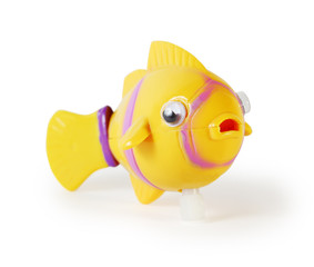 Yellow plastic toy mechanical fish isolated on white background.