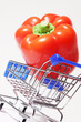 Big appetizing red pepper in shopping cart on white background.