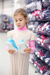 Pretty little girl considers gym shoes and stands near shelves