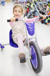 Happy girl rides tricycle and looks at camera in sports store