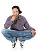Young rapper in jeans and plaid shirt squatting isolated