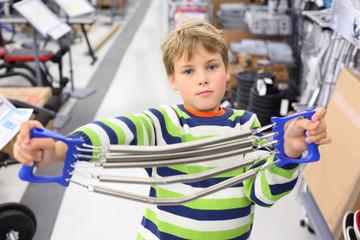 Boy in sports shop holds metal shoulder expander with springs