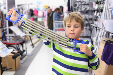 Boy in sports shop tries metal shoulder expander with springs.