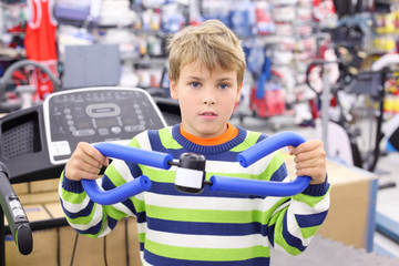 Boy in sports shop tries blue shoulder expander and looks