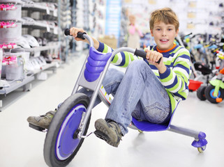 Happy boy rides tricycle and looks at camera in sports store