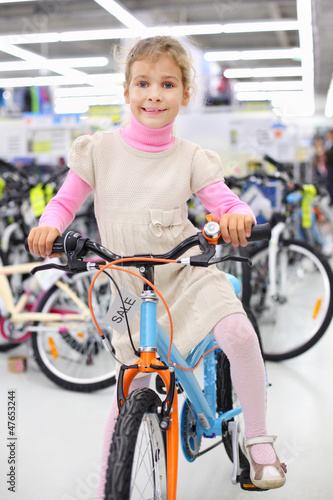Smiling girl sits on bright bicycle and looks at camera