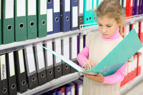 Serious looks at big green folder and stands near to shelves