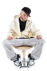 Rapper in yellow jacket sits on yellow chair and looks at camera