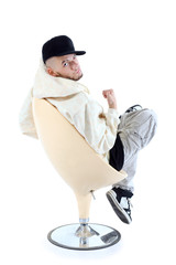 Rapper in yellow jacket sits on yellow chair
