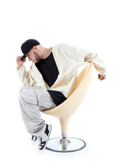 Rapper sits on yellow chair and keeps visor cap isolated