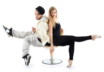 Rapper and ballerina sit on yellow chair and look at camera