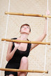 Beautiful young woman in black climbs at bamboo rope ladder