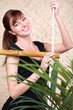 Happy woman in black holds on bamboo rope ladder behind plant