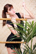 Pretty woman in black holds on bamboo rope ladder