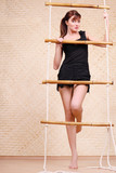 Beautiful young woman in black holds on bamboo rope ladder
