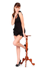 Girl in black dress stands beside small round table isolated