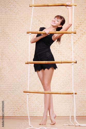 Beautiful smiling woman in black holds on bamboo rope ladder