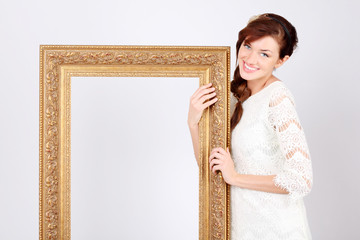 Beautiful smiling woman in white dress holds big gilt frame.