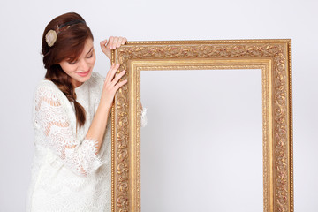 Beautiful smiling woman in white dress holds big gilt frame