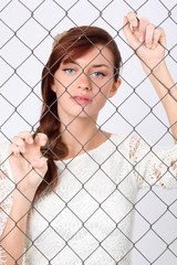 Beautiful woman in white dress stands behind metal mesh
