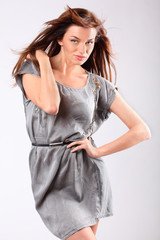 Beautiful young woman in grey dress touches shoulder