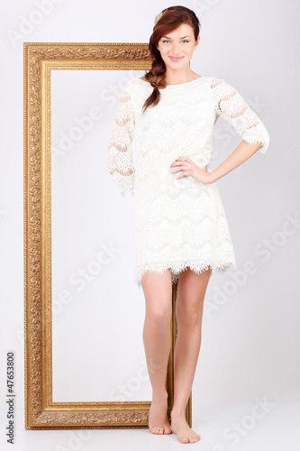 Beautiful woman in white dress stands in front of big gilt frame