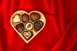 chocolate pralines in golden heart shape box