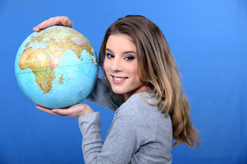 Attractive young woman holding a globe