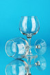 Two empty wine glasses on color background