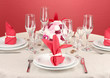 Table setting in red tones on color  background