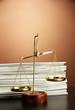 Gold scales of justice and folders on brown background