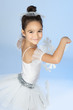 Beautiful little dancer, ballerina in white dress over blue