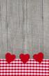 Drei rote Herzen als Grußkarte auf Holz