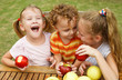 three happy children sitting at the table and eat apples