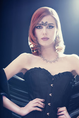 Fashion women in corset. Photo with backlight.