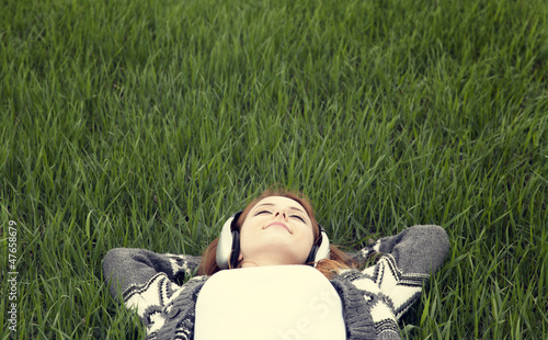 Young with headphones lying down at green grass.