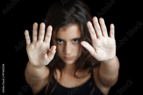 Serious hispanic girl signaling to stop isolated on black
