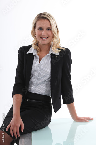 Businesswoman perched on her desk