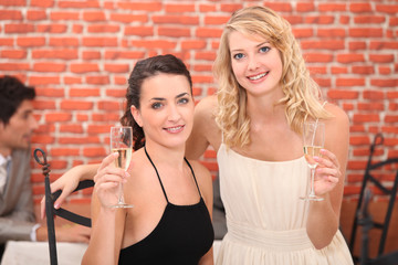 two girlfriends drinking champagne
