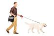 Full length portrait of a guy with shoulder bag walking a dog